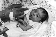 In her hospital bed, one day old Gabriella holds onto BooBoo, her mother. Six pounds, nine ounces. June 25th 1997